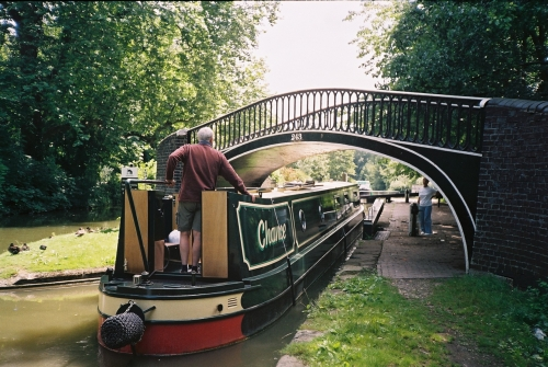 JB_Oxford_canal_boat_entering_lock_bridge_above.jpg